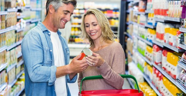 Smiling couple holding canned food at supermarket; Shutterstock ID 343505510; PO: 666